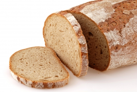 fresh slice of bread: Loaf of a German bread in front of a white background