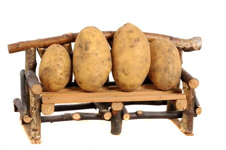 potato basket: Fresh harvested potatoes on a seating bank as symbol for couch potatoes Stock Photo