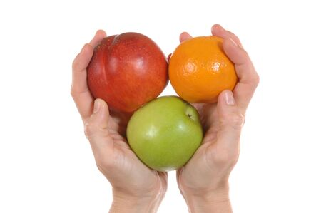 Some fresh fruit in woman�s hand in front of white background photo