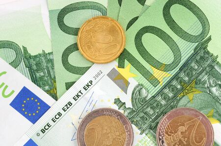 100 Euro bills and some coins in front of a white studio background photo