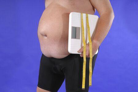 hombre comiendo: Hombre gordo delante de un fondo azul Foto de archivo