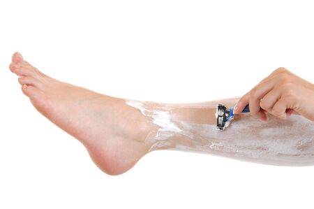 wellbeeing: Young woman is shaving her legs in front of a white background Stock Photo