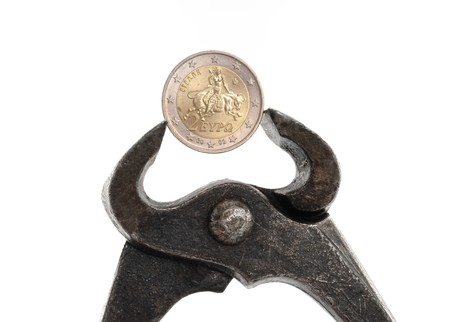 Greek Euro coin in rusty pliers as symbol for the fincancial problems of that country photo