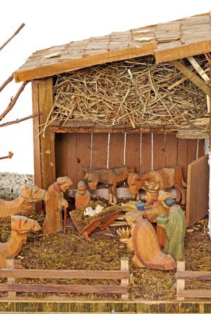 Old handmade nativity scene in front of a white background
