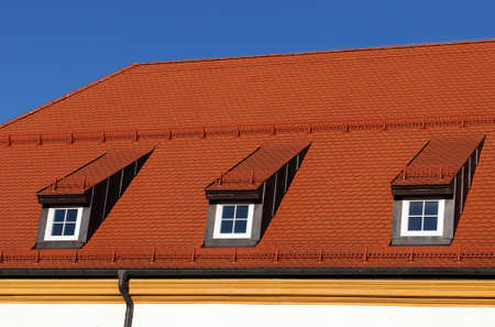 redbrick: New, red roof in front of a blue sky