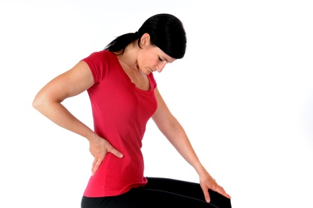 Young woman is holding her spine in front of a white studio background