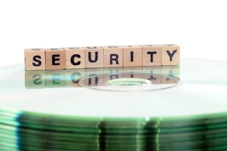 The word security written in wooden letters standing on a computer-CD Stock Photo - 11576839