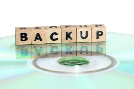 The word backup written in wooden letters standing on a computer-CD Stock Photo - 11576717