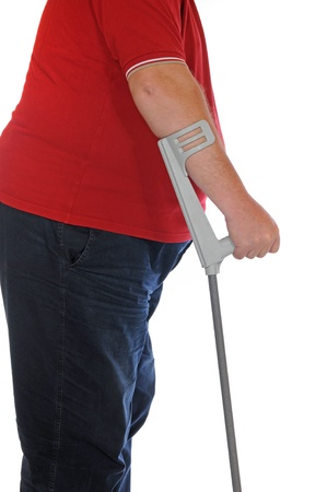 Patient with crutches in front of a white background photo