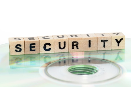 schriftzug: The word security written in wooden letters standing on a computer-CD Stock Photo
