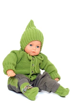 babycare: Handknitted baby dress in front of a white background