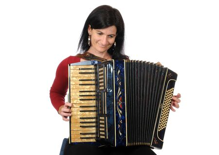 aerophone: Dark haired woman with accordion in front of a white background