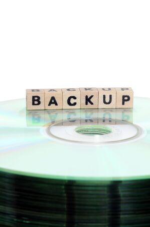 cd rw: The word backup written in wooden letters standing on a computer-CD Stock Photo