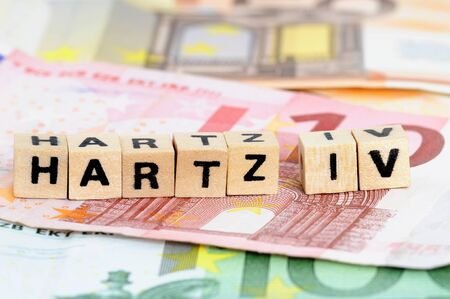 The letters Hartz IV, standing for social benefits in Germany, standing on Euro-currency with selective focus