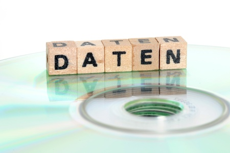 cd rw: The word Daten  = data   written in wooden letters standing on a computer-CD