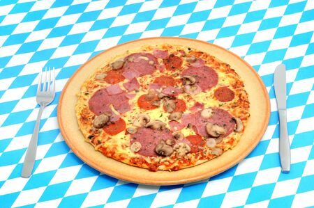 whote: Fresh pizza with salami and white mushrooms on a table, decorated in the colors of Bavaria white and blue