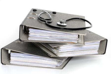equipos medicos: Carpetas de archivos con el estetoscopio en el frente de fondo blanco