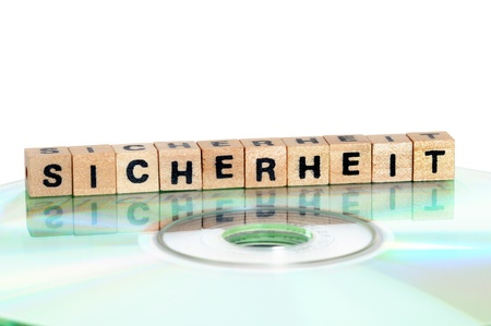 cd rw: The word Sicherheit   = security  written in wooden letters standing on a computer-CD Stock Photo