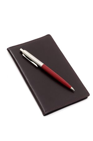 notieren: Dark red notepad with ballpoint pen in front of a white background Stock Photo