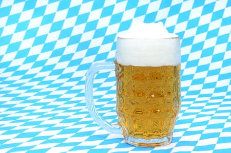 A fresh glass of bavarian beer in front of a white-blue background, the country colors of Bavaria in Germany Stock Photo - 13330446
