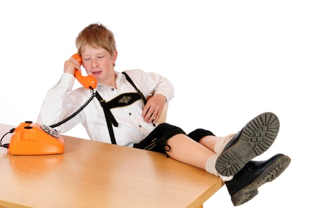 suspender: Boy at an old, orange phone Stock Photo
