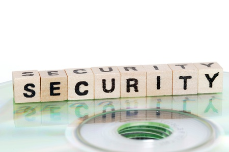 The word security written in wooden letters standing on a computer-CD Stock Photo - 13361724