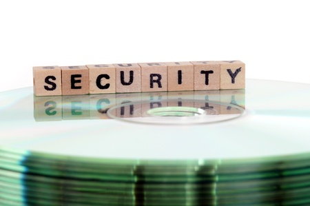 The word security written in wooden letters standing on a computer-CD Stock Photo - 13788183