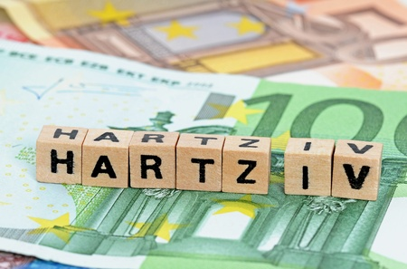 iv: The letters Hartz IV, standing for social benefits in Germany, standing on Euro-currency with selective focus