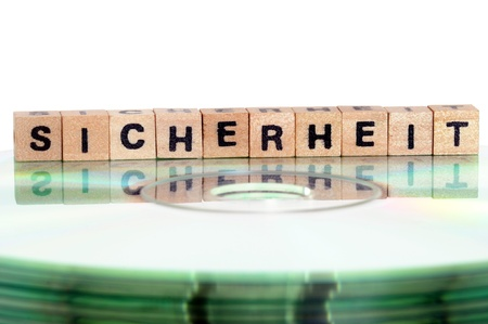 The word Sicherheit ( = security) written in wooden letters standing on a computer-CD Stock Photo - 14237959