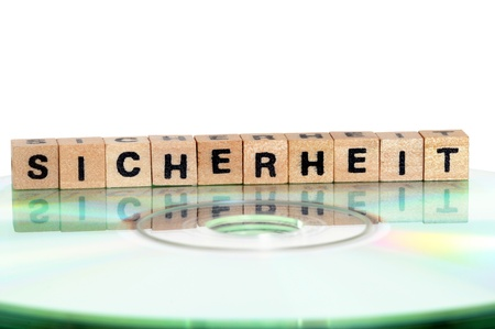 schriftzug: The word Sicherheit ( = security) written in wooden letters standing on a computer-CD