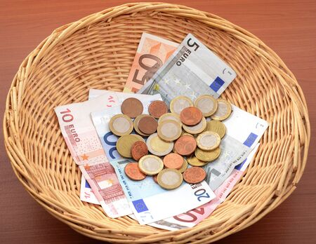 Church donations in a brown basket Stock Photo