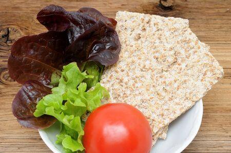 Bowl with leaf lettuce, tomato and crispbread photo