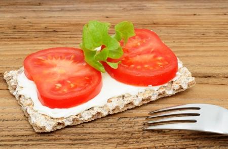 Crispbread with cream cheese and tomato photo