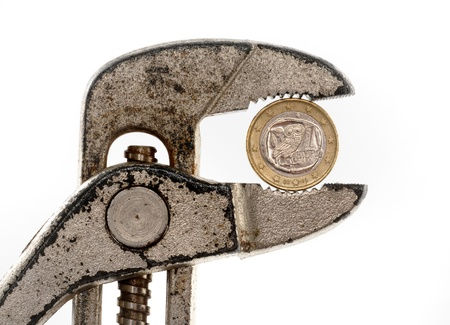 Greek Euro coin in rusty pliers as symbol for the fincancial problems of that country