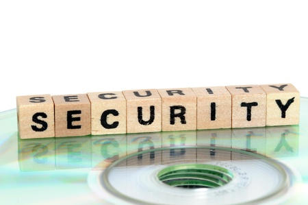 The word security written in wooden letters standing on a computer-CD Stock Photo - 14699514