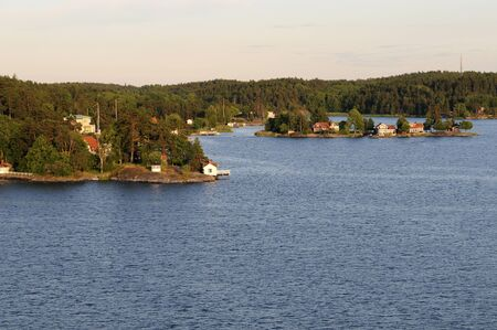 scandinavian peninsula: The archipelago of Stockholm with its small summer houses and saunas in the evening light Stock Photo