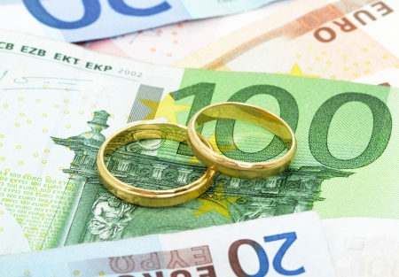 Two wedding rings and money as symbol für an expensive alliance Stockfoto