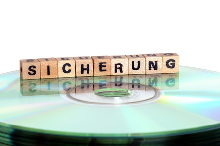 schriftzug: The word Sicherung ( backup) written in wooden letters standing on a computer-CD Stock Photo