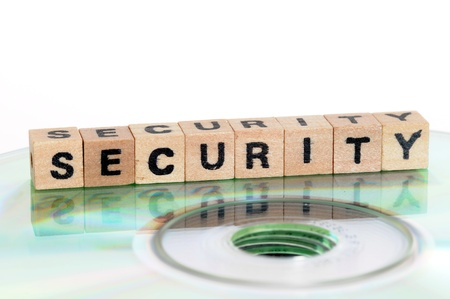 The word security written in wooden letters standing on a computer-CD Stock Photo - 15465700