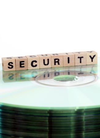 The word security written in wooden letters standing on a computer-CD Stock Photo - 15539431