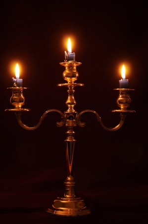 Old candlestick holder in front of a dark red background Stock Photo