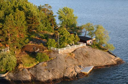 The archipelago of Stockholm with its small summer houses and saunas in the evening light photo