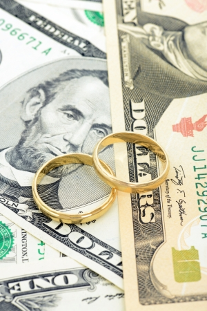 wedding rings: Two wedding rings and money as symbol f�r an expensive alliance Stock Photo