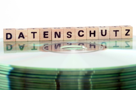 schriftzug:  The word Datenschutz (= data protection) written in wooden letters standing on a computer-CD