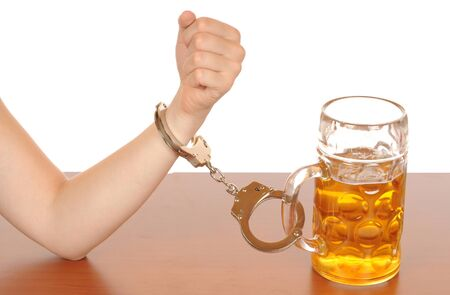 alcohol abuse: Glas of beer with handcuffs as symbol for alcohol abuse Stock Photo