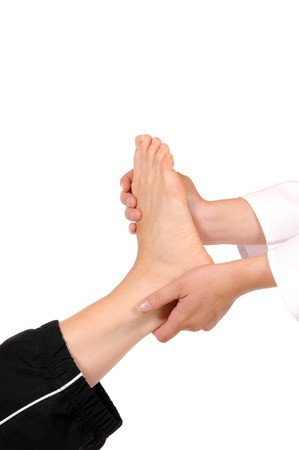 Foot massage of a young woman in front of a white background photo
