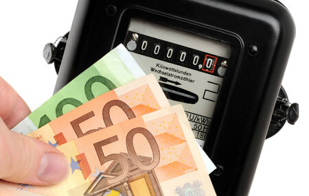 electricity meter: Old electricity meter and Euro-banknotes in front of a white background Stock Photo
