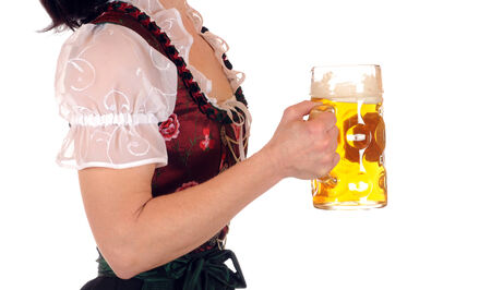 A young woman in Bavarian Dirndl is holding a stein with one liter beer