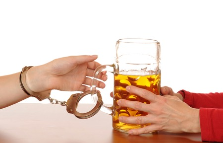 Glas of beer with handcuffs as symbol for alcohol abuse photo