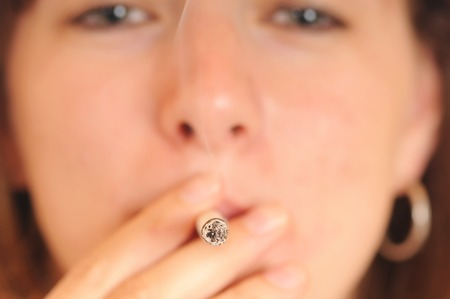 A young woman is smoking a cigarette photo
